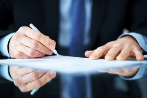 Closeup portrait of a business man hand signing on document